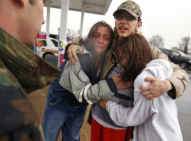 Dacia Winters, left, embraces Ryan Ficca, center, and Stormy Winters after they were evacuated in a Louisiana National Guard high water vehicle from rising floodwaters in Bossier Parish, La., Thursday, March 10, 2016. Heavy rain has forced evacuations and caused flash flooding for more than a day. (Photo by Gerald Herbert/AP Photo)