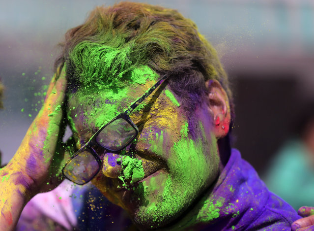A young man is smeared in powdered colors by his friend as they take part in Holi festival celebrations at Durgiana Temple in Amritsar, India, 20 March 2019. Holi is observed at the end of the winter season on the last full moon day of the lunar month Phalguna, which usually falls in the later part of February or March and is celebrated by people throwing colored powder and colored water at each other. (Photo by Raminder Pal Singh/EPA/EFE)