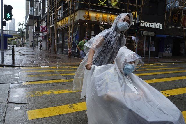 People make their way on an empty street as Typhoon Kompasu passes in Hong Kong Wednesday, October 13, 2021. Hong Kong suspended classes, stock market trading and government services as the typhoon passed south of the city Wednesday. (Photo by Vincent Yu/AP Photo)