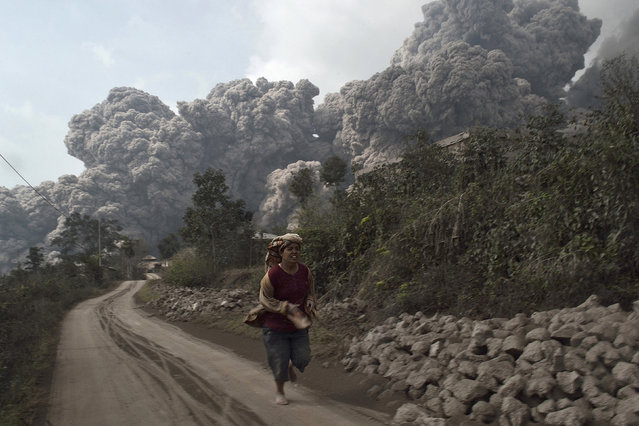 A villager run as Mount Sinabung erupt at Sigarang-Garang village in Karo district, Indonesia's North Sumatra province, February 1, 2014. Four people died and more than 28, 000 villagers have been evacuated since authorities raised the alert status for the volcano to the highest level in November 2013, local media reported on Saturday. (Photo by Reuters/Stringer)