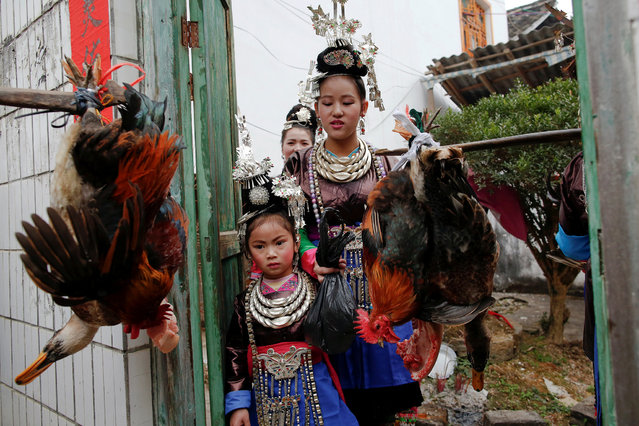 "Ethnic ""Kam"" (also known as Dong) women walk with a child as they carry poles with live chicken and ducks during a traditional wedding ritual. In the 1990s the village introduced a modified version of the ceremony that still involves young men tearing the live birds from the poles carried by the brides. (Photo by Tyrone Siu/Reuters)"