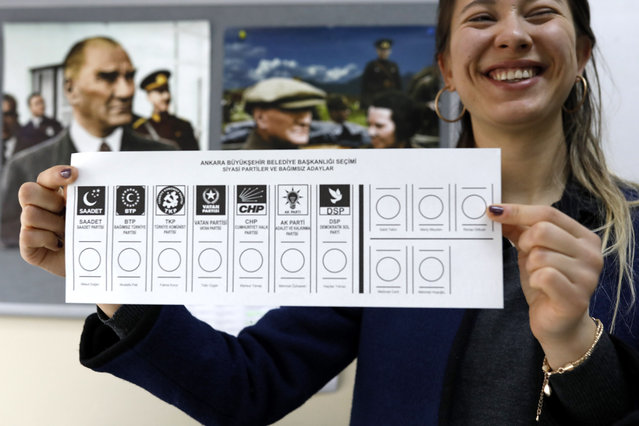 An official female shows the ballot voting paper with names and the parties a polling station during the municipal elections in Ankara, Turkey, Sunday, March 31, 2019. Turkish citizens have begun casting votes in municipal elections for mayors, local assembly representatives and neighborhood or village administrators that are seen as a barometer of Erdogan's popularity amid a sharp economic downturn. (Photo by Burhan Ozbilici/AP Photo)