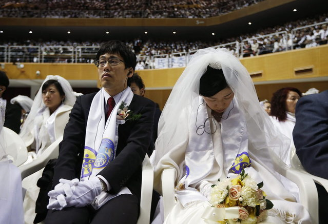 A bride falls asleep next to her groom during a mass wedding ceremony of the Unification Church at Cheongshim Peace World Centre in Gapyeong, about 60 km (37 miles) northeast of Seoul February 12, 2014. (Photo by Kim Hong-Ji/Reuters)