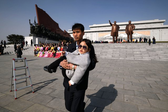 "A man carries a child after paying their respects before the statues of late North Korean leaders Kim Il Sung and Kim Jong Il, as part of celebrations marking the anniversary of the birth of Kim Il Sung, known as the ""Day of the Sun"", on Mansu hill in Pyongyang on April 15, 2019. (Photo by Ed Jones/AFP Photo)"