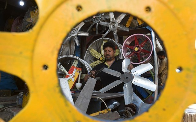 A Pakistani man repairs a fan at his workshop in Lahore on April 9, 2019. (Photo by Arif Ali/AFP Photo)