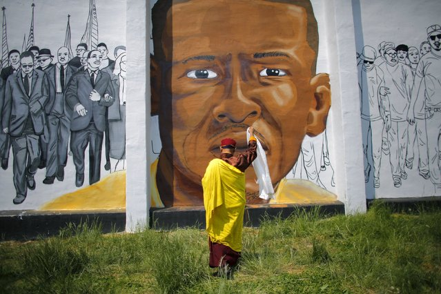 Gyalwang Drukpa, a Buddhist leader from South Asia, prays in front of a mural of Freddie Gray in Baltimore, Maryland, May 7, 2015. Gray, 25, sustained spinal injuries after being arrested and died on April 19. (Photo by Carlos Barria/Reuters)