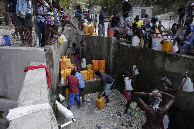 Haitians fill containers with water as others take a bath with water from a pipe in Port-au-Prince, Haiti, March 3, 2016. March 22 marks World Water Day. (Photo by Andres Martinez Casares/Reuters)