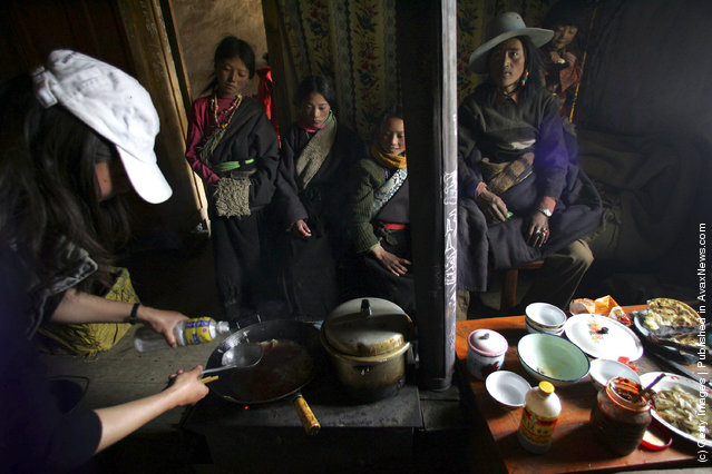 Tibetan students of the Xiangnong primary school watch a tourist to cook lunch