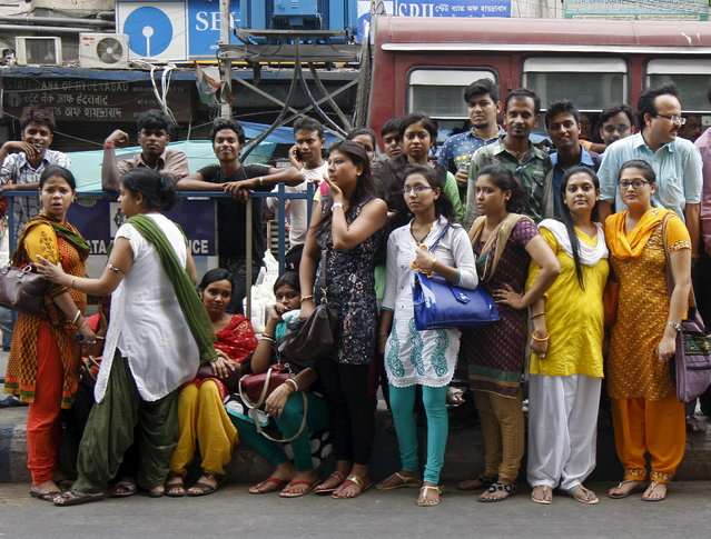 People stand on a road divider after vacating their office buildings following an earthquake in Kolkata, India, May 12, 2015. (Photo by Rupak De Chowdhuri/Reuters)