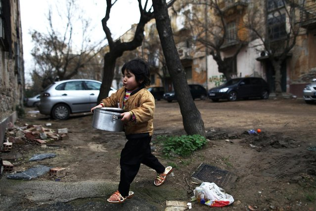 In this Monday, February 20, 2012 file photo a child goes to receive food distributed by a charity organization in Athens. (Photo by Petros Giannakouris/AP Photo)