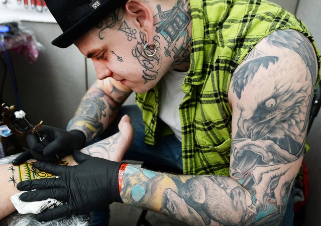 Tattoo artists works at the 2017 Tattoo Collective event at the Old Truman Brewery in London, England on February 17, 2017. (Photo by PA Wire)