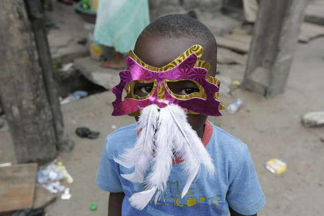 A child wears a mask and watches performers dance through the street during the Lagos Carnival, Nigeria, Saturday May 9, 2015. (Photo by Sunday Alamba/AP Photo)