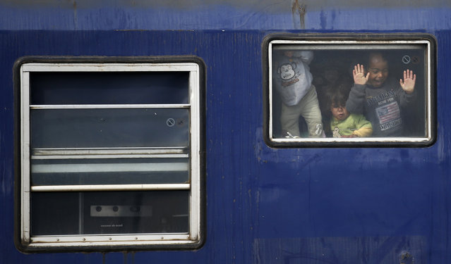 Migrant children look from inside a rail car at a train station near a makeshift refugee camp at the northern Greek border point of Idomeni, Greece, Monday, March 28, 2016. (Photo by Darko Vojinovic/AP Photo)