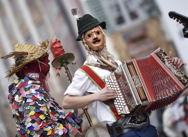 Carnival revelers with traditional masks and costumes parade in the Bavarian town of Mittenwald, Germany, Thursday, February 23, 2017. (Photo by Angelika Warmuth/AP Photo)