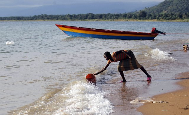 A Burundian refugee girl collects water on the shores of Lake Tanganyika in Kagunga village as they gather in Kigoma region of western Tanzania, to wait for MV Liemba to transport them to Kigoma township, May 17, 2015. (Photo by Thomas Mukoya/Reuters)