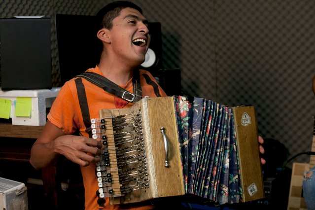 In this Friday, April 24 photo, Fernando Lopez Ramirez plays an accordion made out of discarded wooden shelves, boxes, wallpaper and typewriter keys during a jam session at a popular neighborhood in Mexico City. (Photo by Marco Ugarte/AP Photo)