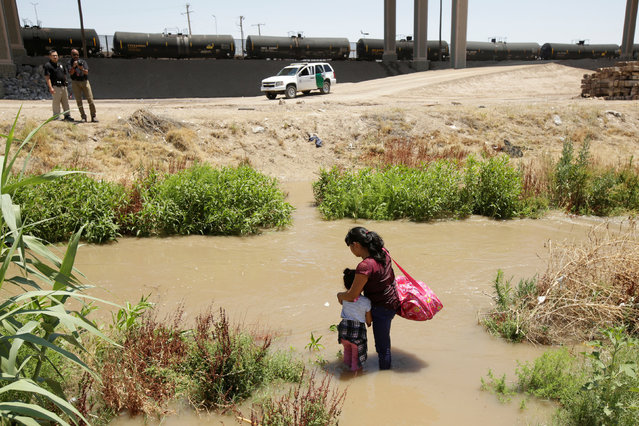 Migrants from Guatemala are seen on the banks of the Rio Bravo river before crossing illegally into the United States to turn themselves in to request asylum in El Paso, Texas, U.S., as seen from Ciudad Juarez, Mexico June 11, 2019. (Photo by Jose Luis Gonzalez/Reuters)