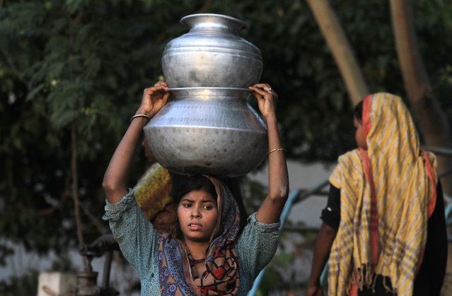 A Pakistani girl carries clean water to her  home in Lahore's slums in Pakistan, Wednesday, April 22, 2015. There is a scarcity of fresh drinking water in Pakistan among a population of around 180 million. (Photo by K. M. Chaudary/AP Photo)