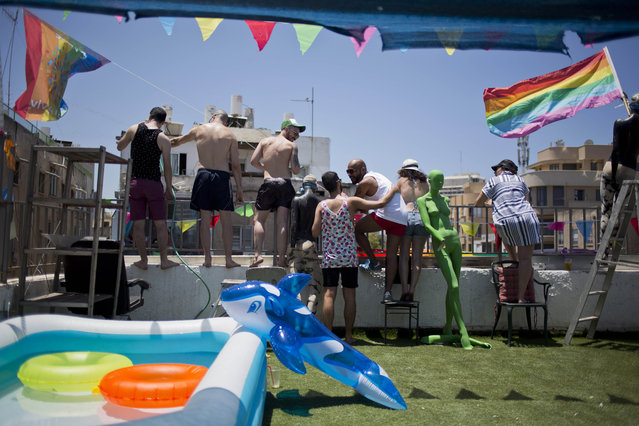 People watch from their roof top at the annual Gay Pride Parade in Tel Aviv, Tel Aviv, Israel, Friday, June 12, 2015. Thousands of bare-chested muscular men, drag queens in heavy makeup and high heels, women in colorful balloon costumes and others partied at Tel Aviv's annual gay pride parade on Friday, the largest event of its kind in the region. (AP Photo/Ariel Schalit)
