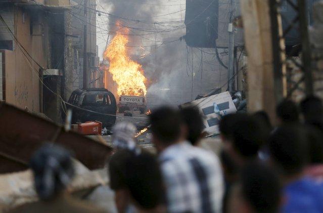 Kurdish gunmen look at the burning car of a Shi'ite militiaman in Tuz Khurmato, Iraq, April 24, 2016. (Photo by Goran Tomasevic/Reuters)