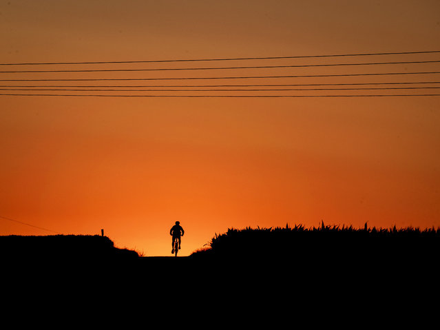 A man rides his bike up a hill just before the sun rises in Frankfurt, Germany, Wednesday, July 3, 2019. (Photo by Michael Probst/AP Photo)