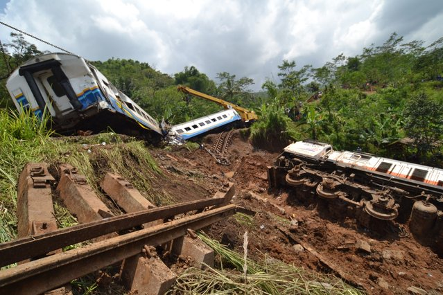 Workers lift up a derailed train wagon with a crane in Tasikmalaya on the Indonesian island of Java on April 5, 2014. A landslide triggered by heavy rain derailed the train as it travelled through Indonesia's main island of Java on April 4, leaving three people dead, an official said. (Photo by AFP Photo/Bustomi)