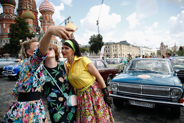 Woman take a selfie by a vintage car during the 2019 GUM Motor Rally featuring classic cars in Moscow, Russia on July 28, 2019. (Photo by Artyom Geodakyan/TASS via Getty Images)