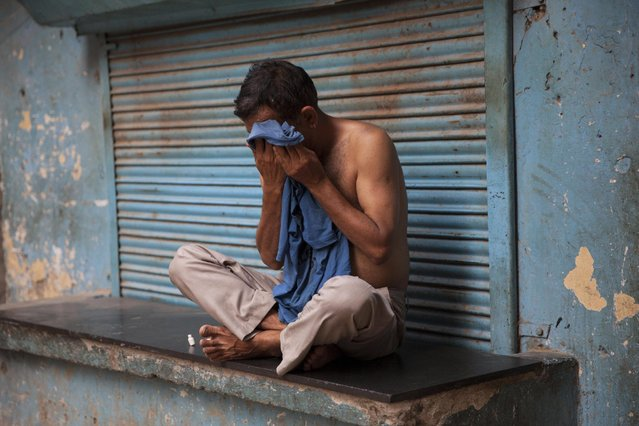 An Indian man wipes sweat off his face on a hot summer day in New Delhi, India, Sunday, May 24, 2015. Heat wave has tightened its grip over most parts of the country. More than 200 people have died since mid-April in a heat wave sweeping two southeast Indian states, Andhra Pradesh and Telangana, officials said Saturday. (Photo by Tsering Topgyal/AP Photo)