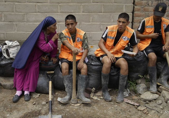 A woman from a religious sect, who lost her home to flooding, gives a religious lecture to soldiers taking a rest from cleaning a clogged river in the Chosica district of Lima, Peru, Sunday, March 19, 2017. (Photo by Martin Mejia/AP Photo)