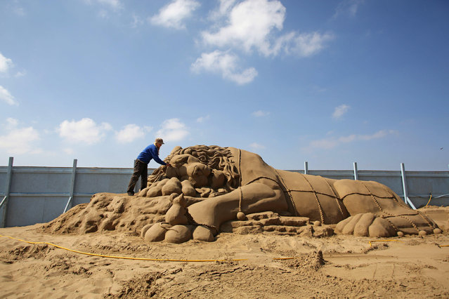 "Artist Rachel Stubbs works on the final touches of a sand sculpture she has built as part of this year's ""Once Upon a Time"" themed annual Weston-super-Mare Sand Sculpture festival on April 16, 2014 in Weston-Super-Mare, England. (Photo by Matt Cardy/Getty Images)"