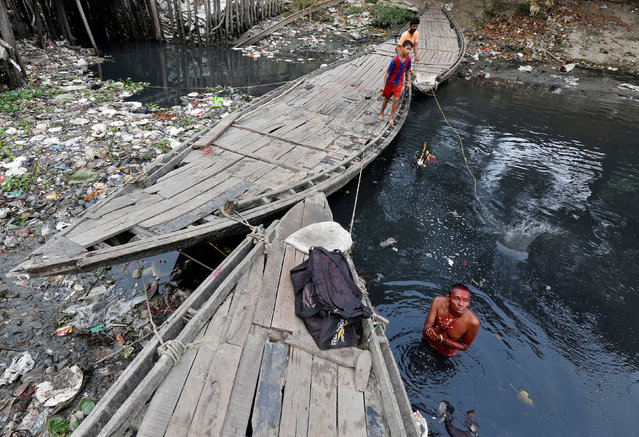 A man offers a prayer as he takes a dip in the polluted waters of Tolly's Nullah in Kolkata, March 22, 2017. (Photo by Rupak De Chowdhuri/Reuters)