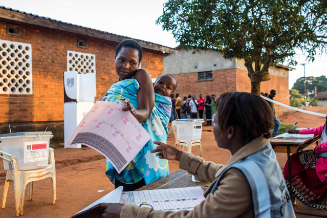 A woman receives a ballot paper at Masasa Primary School polling station in Mzuzu on May 21, 2019. (Photo by Patrick Meinhardt/AFP)