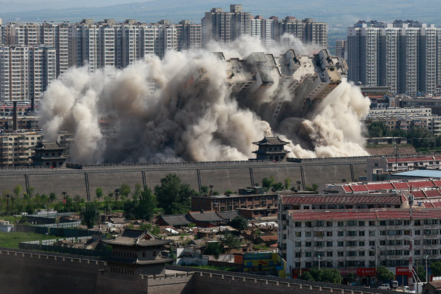 A building crumbles during a controlled demolition conducted to better protect the nearby ancient area of the city in Datong, Shanxi province, China, August 9, 2016. (Photo by Reuters/China Daily)