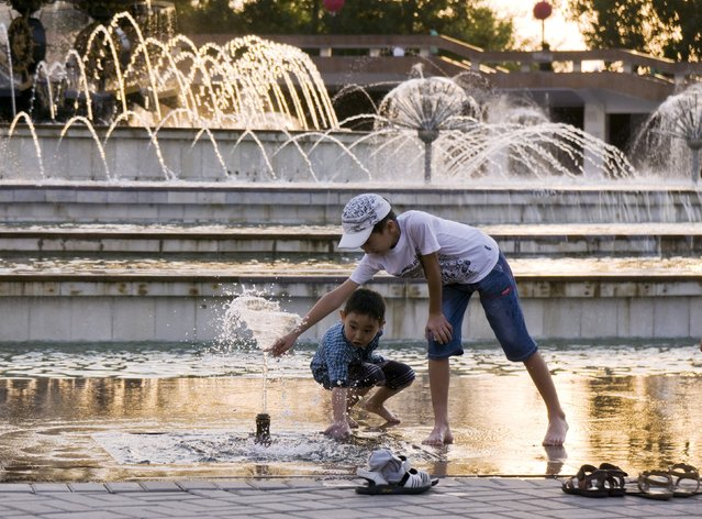 Boys play in a public fountain on the evening of a hot summer day in Almaty, Kazakhstan, July 3, 2015. (Photo by Shamil Zhumatov/Reuters)