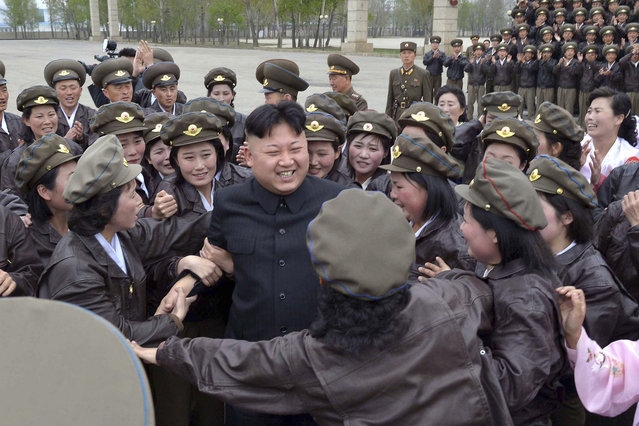 North Korean leader Kim Jong Un is surrounded by some female participants of the first meeting of the airpersons of the Korean People's Army (KPA) during a photo-taking session in Pyongyang April 17, 2014, in this photo released by North Korea's Korean Central News Agency (KCNA) on April 20, 2014. (Photo by Reuters/KCNA)