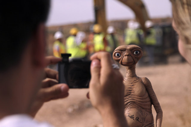 """A man takes a photo of an E.T. doll in Alamogordo, N.M, Saturday, April 26, 2014. Producers of a documentary dug in an southeastern New Mexico landfill in search of millions of cartridges of the Atari """"E.T. the Extra-Terrestrial"""" game that has been called the worst game in the history of video gaming and were buried there in 1983. (Photo by Juan Carlos Llorca/AP Photo)"""