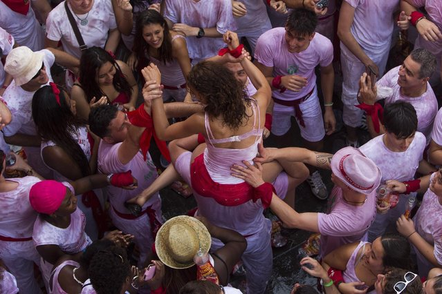 """A girl is held by other revelers during the launch of the """"Chupinazo"""" rocket, to celebrate the official opening of the 2015 San Fermin fiestas in Pamplona, Spain, Monday, July 6, 2015. (Photo by Andres Kudacki/AP Photo)"""