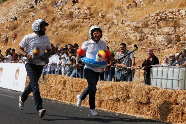 Competitors run to complete the race after crashing their homemade vehicle without an engine during the Red Bull Soapbox Race in Amman, Jordan on September 20, 2019. (Photo by Muhammad Hamed/Reuters)