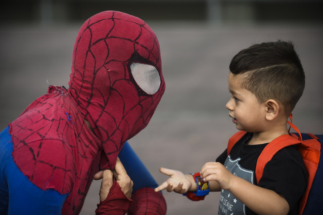 """Colombian Jahn Fredy Duque, dressed as superhero """"Spiderman"""", talks to a little boy while performing on the streets in Bogota, Colombia on April 24, 2017. (Photo by Raul Arboleda/AFP Photo)"""