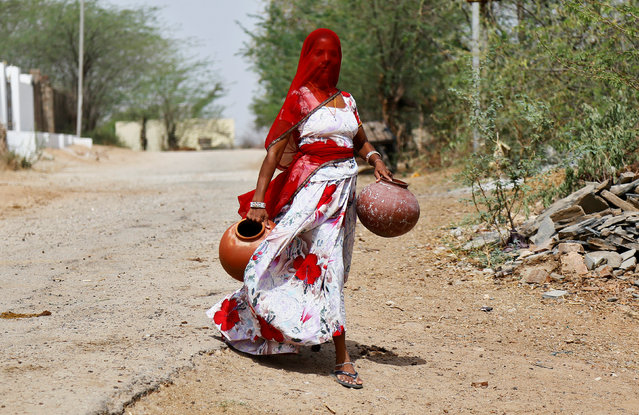 A woman carries earthen pots to fill them with drinking water on a hot summer day, on the outskirts of Ajmer, Rajasthan, India April 25, 2017. (Photo by Himanshu Sharma/Reuters)