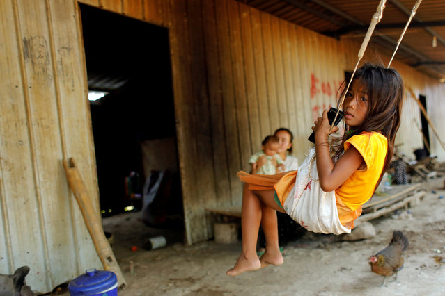 The daughter of a banana plantation worker swings outside her home at a plantation operated by a Chinese company in the province of Bokeo in Laos April 26, 2017. (Photo by Jorge Silva/Reuters)