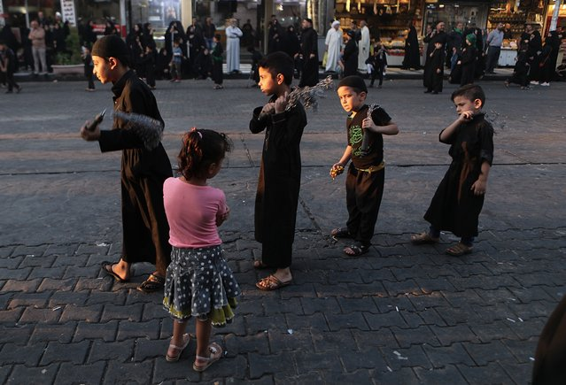 A girl watches Shiite children beat themselves with chains during a Muharram procession in Baghdad, Iraq, Monday, September 9, 2019. Muharram, the first month of the Islamic calendar, is a month of mourning for Shiites in remembrance of the death of Hussein, the grandson of the Prophet Muhammad, at the Battle of Karbala in present-day Iraq in the 7th century. (Photo by Khalid Mohammed/AP Photo)