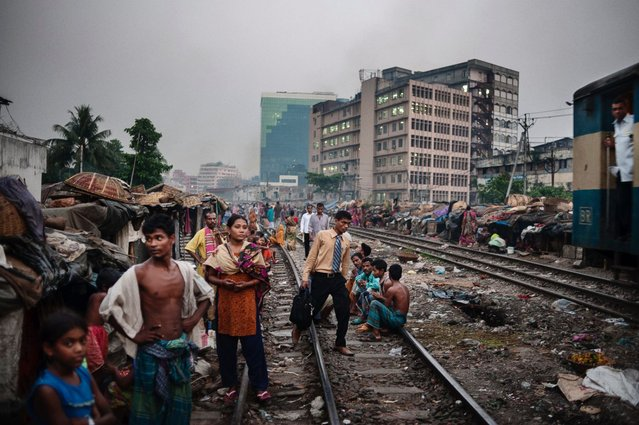 The view of Kawran Bazar slums where thousands of people live alongside the railway lines in Dhaka, Bangladesh. Over the years, Dhaka has seen an influx of newcomers entering the city, some of which are migrants leaving the countryside due to severe flooding and destruction caused by cyclones. (Photo by Alessandro Grassani)