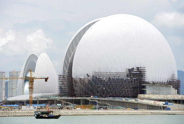 A boat travels past the Zhuhai Opera House under construction off the coast of the Yeli Island, in Zhuhai, Guangdong province, China, July 20, 2015. The opera house, in the shape of two shells, costs about 1.08 billion yuan (170 million USD) and is expected to be completed at the end of this year, local media reported. (Photo by Reuters/Stringer)