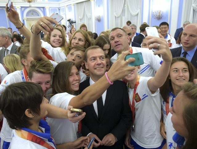Russian Prime Minister Dmitry Medvedev (C) poses for a picture with prizewinners of the 2015 Summer Universiade in Gwangju during a meeting at the Gorki state residence outside Moscow, Russia, July 17, 2015. (Photo by Alexander Astafyev/Reuters/RIA Novosti)