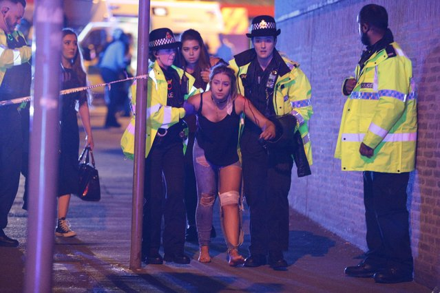 An injured woman is escorted by police after an explosion at the Manchester Arena during a pop concert by US singer Ariana Grande in Manchester, Britain on May 22, 2017. (Photo by Joel Goodman/Rex Features/London News Pictures/Shutterstock via AP Photo)