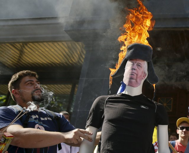 An activist stands next to a mannequin with burning hat which represents the Prosecutor General of Ukraine Viktor Shokin during their anti-corruption rally in front of the Prosecutor General's office in Kiev, Ukraine, July 24, 2015. (Photo by Valentyn Ogirenko/Reuters)