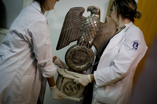 Members of the federal police carry a Nazi statue at the Interpol headquarters in Buenos Aires, Argentina, Friday, June 16, 2017. In a hidden room in a house near Argentina's capital, police discovered on June 8th the biggest collection of Nazi artifacts in the country's history. Authorities say they suspect they are originals that belonged to high-ranking Nazis in Germany during World War II. (Photo by Natacha Pisarenko/AP Photo)