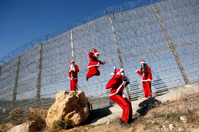 Palestinian children dressed as Santa Claus jump near the Israeli barrier during an anti-Israel protest, near Bethlehem in the Israeli-occupied West Bank on December 23, 2019. (Photo by Mussa Qawasma/Reuters)
