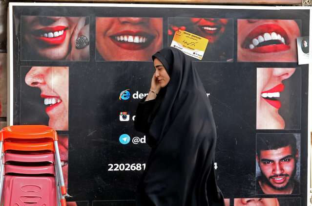 "An Iranian woman walks past a bilboard as she talks on the phone in the capital Tehran, on November 27, 2019. Iran's supreme leader Ayatollah Ali Khamenei praised the country's people for foiling a ""very dangerous"" plot after violence erupted during protests this month against a fuel price hike by as much as 200 percent, as protesters attacked police stations, torched petrol pumps and looted shops, before being quashed within a few days. (Photo by Atta Kenare/AFP Photo)"